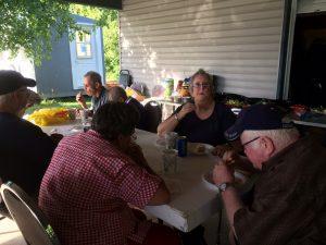 Groupe de personnes âgées mangeant autour d'une table de pique-nique.