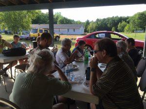 Groupe de personnes mangeant autour d'une table de pique-nique.