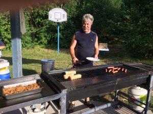 Monsieur devant des saucisses et des pains à hot-dog en train de griller sur un grand BBQ.