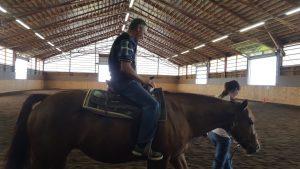Monsieur sur le dos d'un cheval qui avance tranquillement.