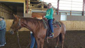 Jeune fille souriante sur le dos d'un cheval immobile.