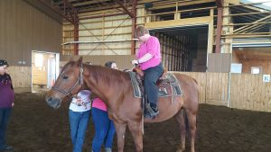 Madame s'assoyant sur le dos d'un cheval.