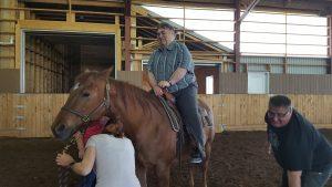 Monsieur souriant sur le dos d'un cheval immobile.