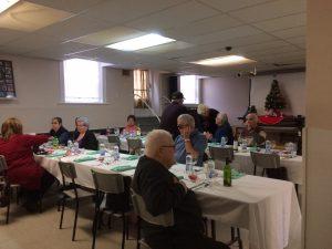 Photo d'une salle avec participants autour d'une table pour un repas de Noël.