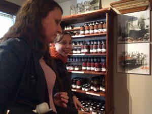 Photo de deux personnes devant une bibliothèque de bouteilles de vins.