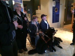 Personnes avec des chiens Mira écoutant une présentation.