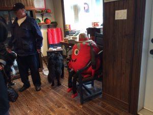 Épouvantail avec un corps semblable à une tomate et assis sur une chaise à l'intérieur.